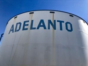 "White lettering spelling out ""Adelanto"" on beautiful green grass with clear blue skies in the background."