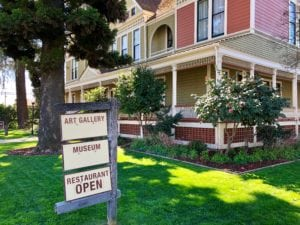 Historic colonial style home with large trees and sign displaying Art Gallery, Museum and Restaurant Open