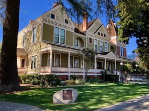 Colonia style house with large trees and beautifully manicured green lawn in historic downtown San Dimas